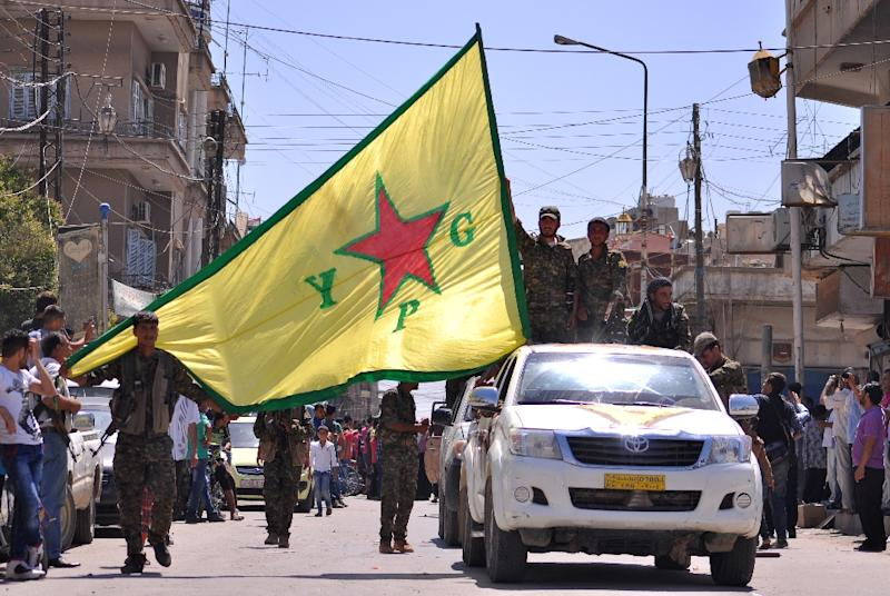 Kurdish People's Protection Units (YPG) fighters wave their flag in northeastern Syrian town of Qamishli in June