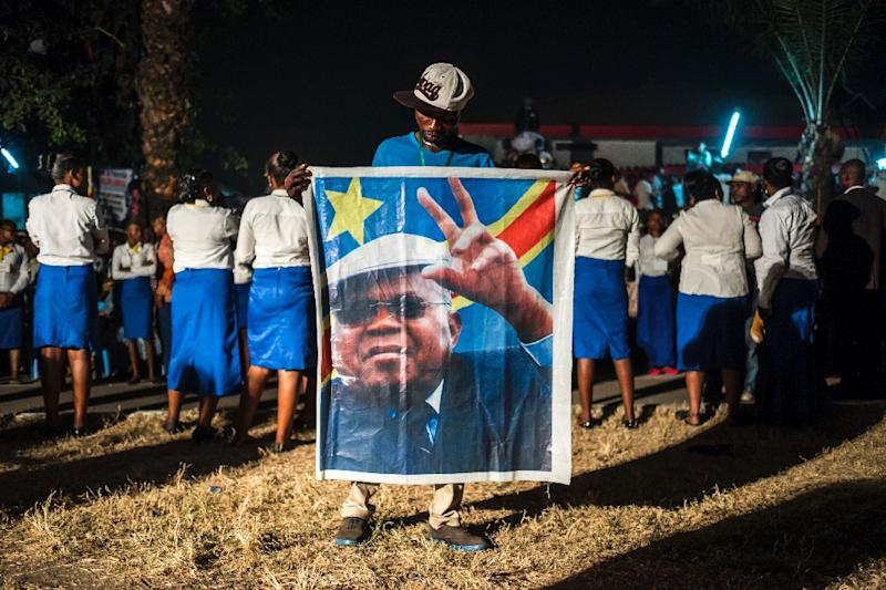 A supporter of the Democratic Republic of Congo's opposition leader Etienne Tshiskedi holds his portrait during a rally in Kinshasa in 2016 (AFP Photo/Eduardo Soteras)