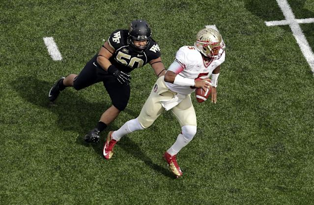 Florida State quarterback Jameis Winston, right, scrambles to avoid Wake Forest defender Nikita Whitlock in the first half of an NCAA college football game in Winston-Salem, N.C., Saturday, Nov. 9, 2013. Florida State won 59-3. (AP Photo/Nell Redmond)