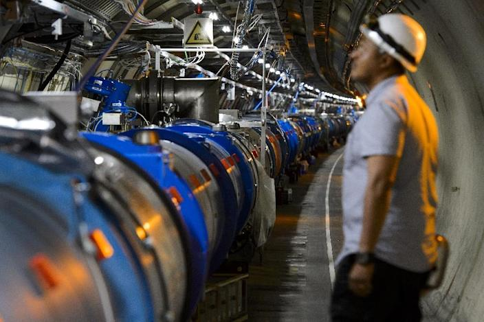 A scientist looks at a section of the European Organisation for Nuclear Research Large Hadron Collider, during maintenance works in Meyrin, near Geneva on July 19, 2013 (AFP Photo/Fabrice Coffrini)