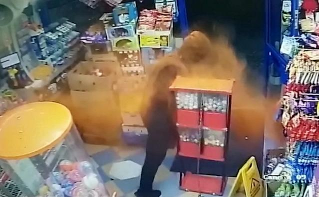 The brave shop owner lobs chilli powder at the thug. (SWNS)