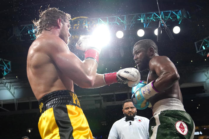 Logan Paul, left, and Floyd Mayweather fight during an exhibition boxing match at Hard Rock Stadium, Sunday, June 6, 2021, in Miami Gardens, Fla. (AP Photo/Lynne Sladky)