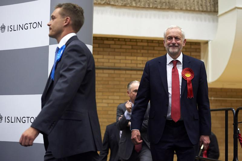 Labour party leader Jeremy Corbyn (R) smiles as he arrives for the results to be declared at the count centre in Islington, London, early in the morning of June 9, 2017, hours after the polls closed in Britain's general election. The main opposition Labour party, led by leftist Jeremy Corbyn, was on course to increase its number of seats from 229 to 266, according to the joint exit poll by Sky, the BBC and ITV. / AFP PHOTO / NIKLAS HALLE'N (Photo credit should read NIKLAS HALLE'N/AFP via Getty Images)