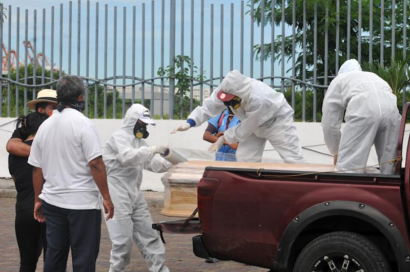 Workers wearing protective suits wrap with plastic a coffin with the remains of a person who died from the coronavirus, outside the morgue of the Hospital General Guasmo Sur in Ecuador. Source: Getty Images