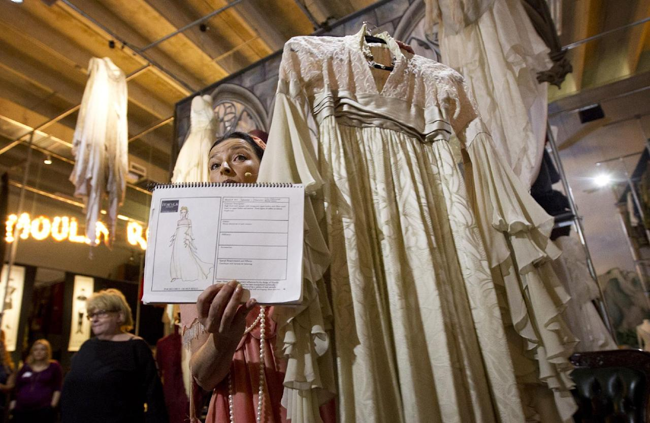 "This Oct, 3, 2012 photo shows Kimberly Wick displaying the costume book and one of the dresses from the play, ""Dracula the Musical"", as she conducts a tour of her costume museum in Pompano Beach, Fla. Marilynn Wick and her daughter Kimberly opened a museum in 2011, showcasing more than one million costumes from nearly 50 shows, guiding daily tours through a non-de script South Florida warehouse against a backdrop of hand painted sets and a marquee replica from storied Broadway theaters like the Winter Garden. (AP Photo/J Pat Carter)"