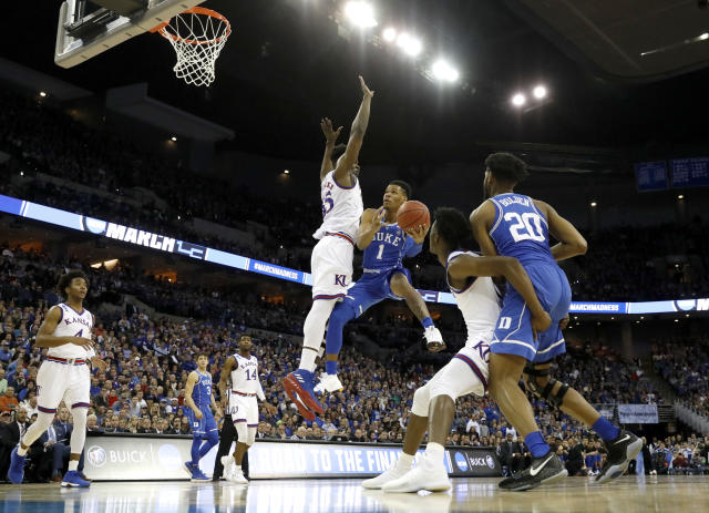 Duke's Trevon Duval (1) shoots around Kansas' Udoka Azubuike (35) during the first half of a regional final game in the NCAA men's college basketball tournament Sunday, March 25, 2018, in Omaha, Neb. (AP Photo/Charlie Neibergall)