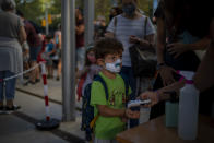A student wearing a face mask to prevent the spread of coronavirus, has his temperature checked, prior to entering the school in Barcelona, Spain, Monday, Sept. 14, 2020. Students in Catalonia and Murcia returned to the classrooms for the first time since schools closed due to the coronavirus pandemic. (AP Photo/Emilio Morenatti)