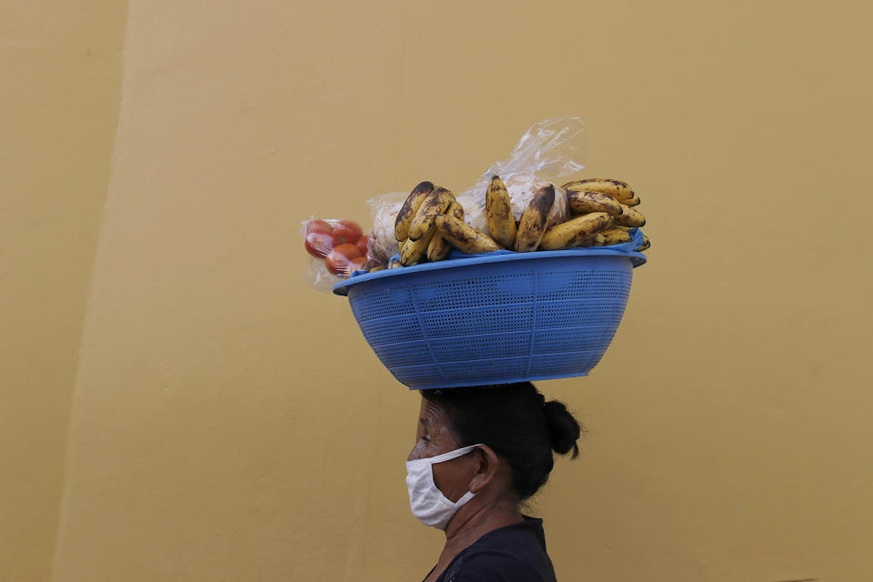 Guillerma Torres, wearing a face mask to curb the spread of the new coronavirus, carries a basket of fruit on her head to sell, on a street in Tegucigalpa, Honduras, Thursday, June 18, 2020. The hospitalization Wednesday of Honduras' president with COVID-19 and pneumonia has drawn attention to another country struggling under the pandemic's strain as cases rise exponentially in the capital. (AP Photo/Elmer Martinez)