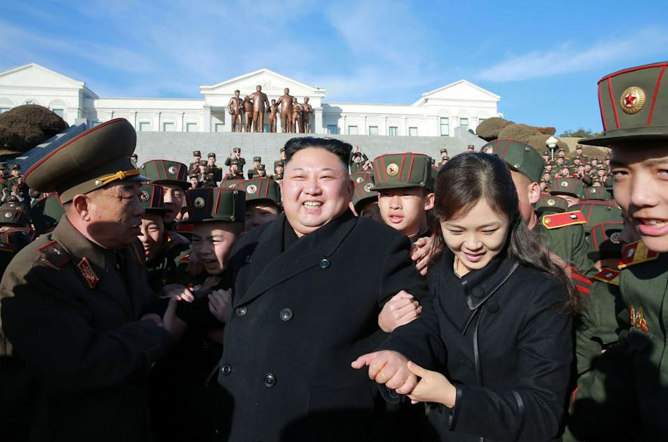 Pictured is Kim Jong-un and his wife Ri Sol-ju surrounded by North Korean military.