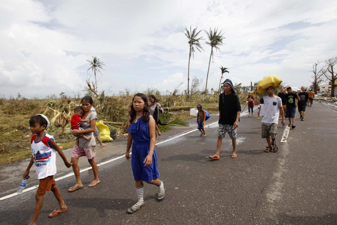 Survivors walk past a damaged town after strong winds brought by super Typhoon Haiyan battered Tacloban city, central Philippines November 9, 2013. Typhoon Haiyan, the strongest typhoon in the world this year and possibly the most powerful ever to hit land battered the central Philippines on Friday, forcing millions of people to flee to safer ground, cutting power lines and blowing apart houses. Haiyan, a category-5 super typhoon, bore down on the northern tip of Cebu Province, a popular tourist destination with the country's second-largest city, after lashing the islands of Leyte and Samar with 275 kph (170 mph) wind gusts and 5-6 meter (15-19 ft) waves. REUTERS/Romeo Ranoco (PHILIPPINES - Tags: DISASTER ENVIRONMENT)