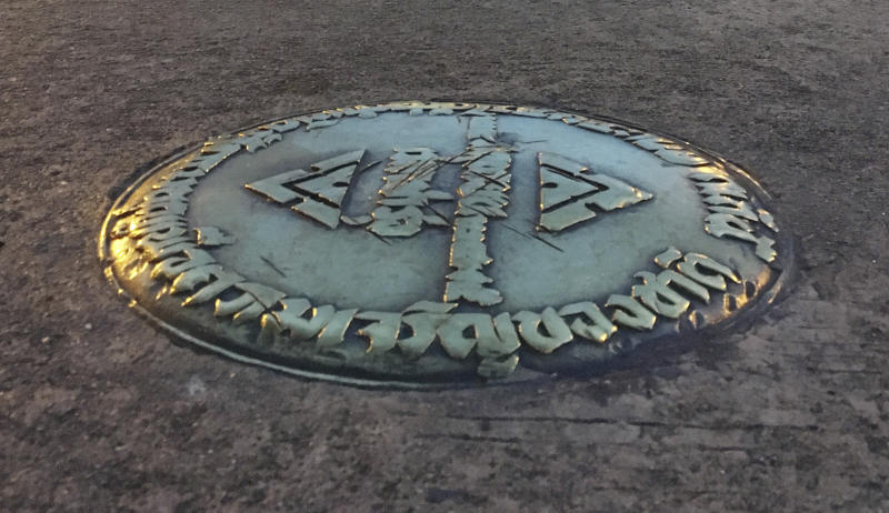 In this Oct. 2, 2016, photo, a small bronze plaque commemorating Thailand's 1932 revolution rests in the pavement of the Royal Plaza in Bangkok, Thailand. In early April, the plaque was mysteriously removed by parties unknown and substituted by one praising the Chakri Dynasty, whose 10th king took the throne last December. A disinclination by the authorities to find those responsible adds another element of mystery. (AP Photo/Apichart Khunnawatbandit)
