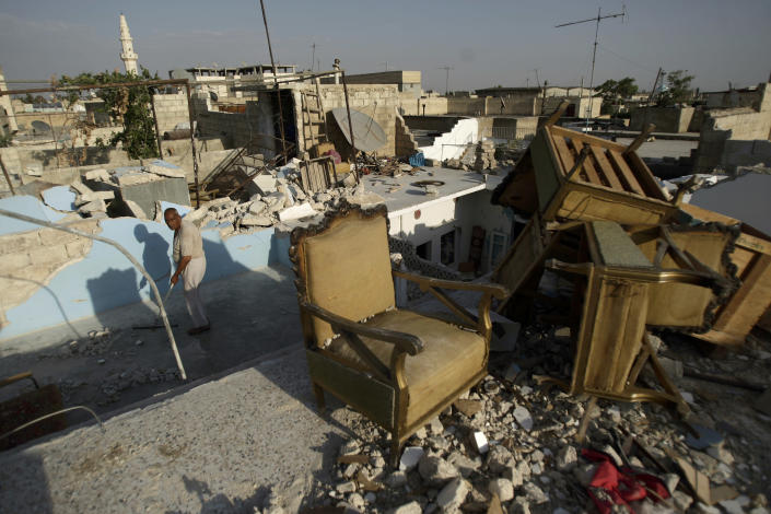 A Syrian man cleans the rooftop of his house which was partly destroyed partly in a government airstrike, in the Syrian town of Azaz, on the outskirts of Aleppo, Friday, Aug. 31, 2012. (AP Photo/Muhammed Muheisen)
