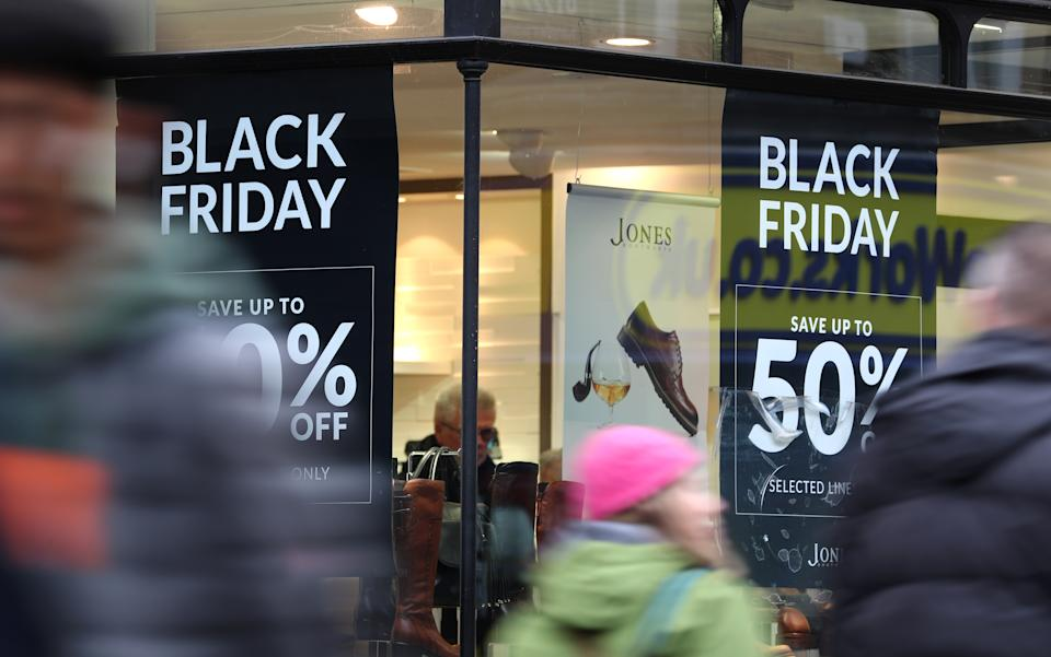 Shops in Canterbury, Kent, display offer posters ahead of Black Friday sales.