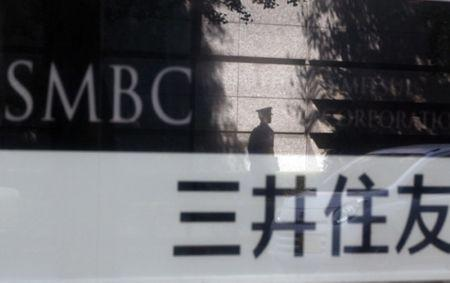 FILE PHOTO - File photo of a security guard reflected on a sign outside a branch of Sumitomo Mitsui Banking Corporation in Tokyo