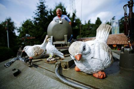 """Gary Blackburn, a 53-year-old tree surgeon from Lincolnshire, Britain, poses atop of a demilitarised Centurion tank decorated with peace doves at his British curiosities collection called """"Little Britain"""" in Linz-Kretzhaus, south of Germany's former capital Bonn, Germany, August 24, 2017. Picture taken August 24, 2017. REUTERS/Wolfgang Rattay"""