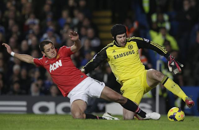 Chelsea's goalkeeper Petr Cech, right, is tackled by Manchester United's Javier Hernandez during the English Premier League soccer match between Chelsea and Manchester United at Stamford Bridge stadium in London, Sunday, Jan. 19, 2014. (AP Photo/Matt Dunham)
