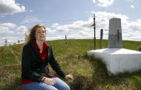 Lynda Hartley sits by a border marker at the site of a proposed wind turbine across the border from Stanstead, Quebec on Friday, May 11, 2012. A Vermont wind power developer and two dairy farmers in the border community of Derby Line say they've been surprised at the level of opposition to a plan to build two turbines that has been coming from the Quebec town of Stanstead.(AP Photo/Toby Talbot)