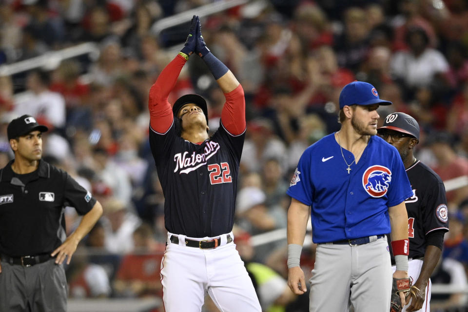 Washington Nationals' Juan Soto (22) gestures as he stands on first with a single next to Chicago Cubs first baseman Patrick Wisdom, right, during the seventh inning of a baseball game Friday, July 30, 2021, in Washington. The Nationals won 4-3.(AP Photo/Nick Wass)
