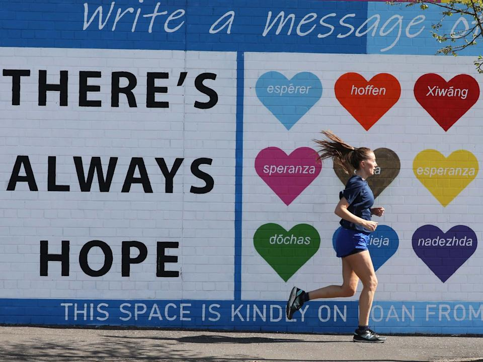 A woman runs past a mental health mural on the Falls road in west Belfast: PA