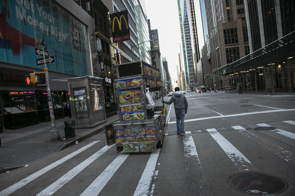 A food truck vendor pushes his cart down an empty street near Times Square in New York, on March 15, 2020. (AP Photo/Wong Maye-E)