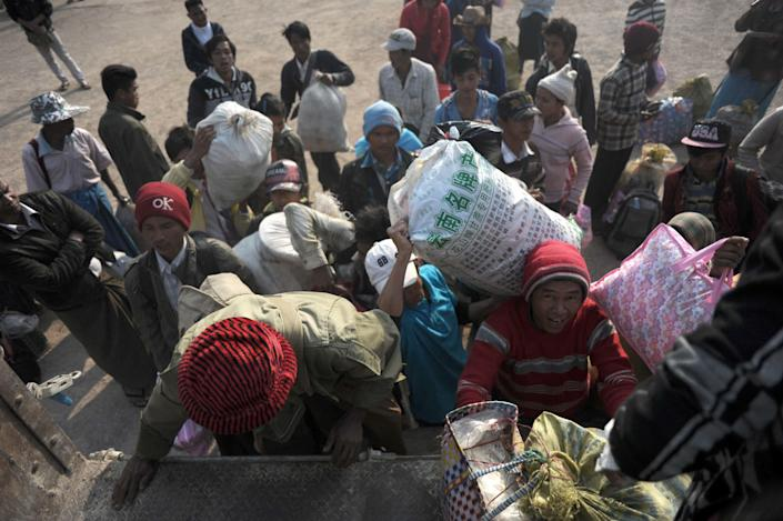 Residents who fled from conflict areas near the Myanmar-China border load belongings onto a truck before moving to a refugee camp in Mandalay from Lashio, northern Myanmar on February 18, 2015 (AFP Photo/Ye Aung Thu)