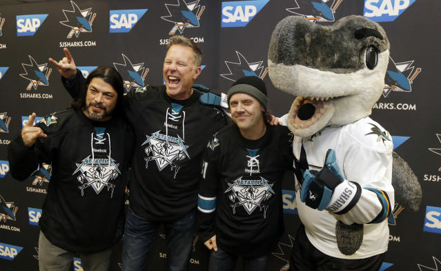 Metallica members, from left, Robert Trujillo, James Hetfield and Lars Ulrich pose with San Jose Sharks jerseys alongside team mascot SJ Sharkie before an NHL hockey game against the Los Angeles Kings Wednesday, Jan. 21, 2015, in San Jose, Calif. (AP Photo/Marcio Jose Sanchez)