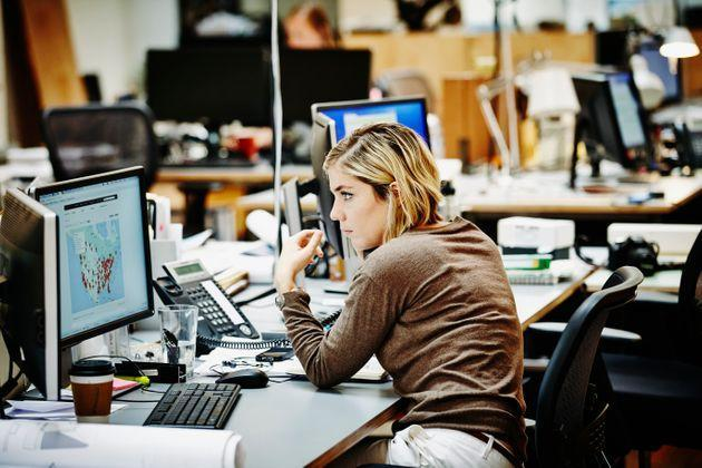 Female architect at workstation in office reviewing project with client on the phone (Photo: Thomas Barwick via Getty Images)