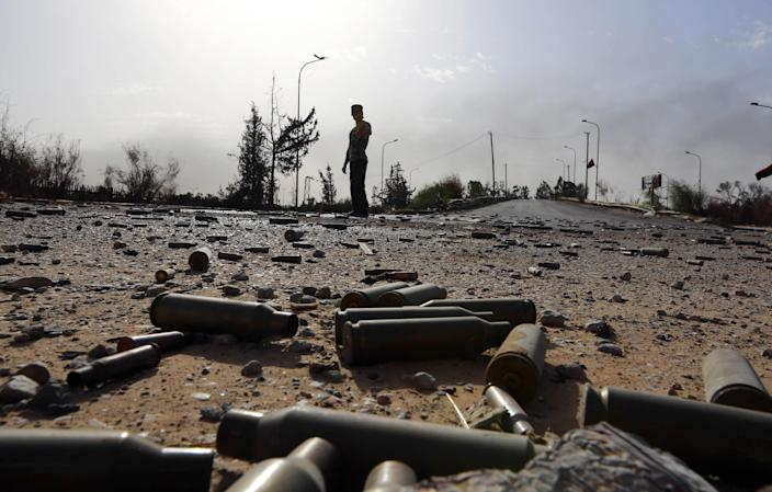 Bullet shells litter the ground as a member of the Islamist-linked militia of Misrata walks past following battles in the area of Tripoli's International airport, on August 21, 2014 (AFP Photo/Mahmud Turkia)