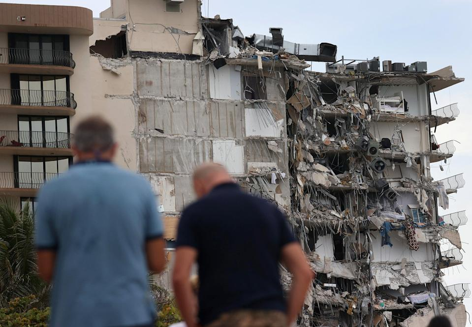 People look at a portion of the 12-story Champlain Towers South condo building that partially collapsed on Thursday  (Getty Images)