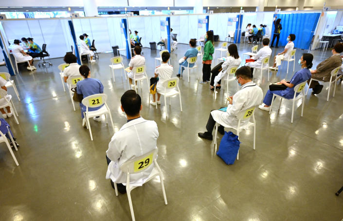 Doctors and nurses wait to receive China's Sinovac COVID-19 coronavirus vaccine at a community vaccination centre in Hong Kong Tuesday, Feb. 23, 2021. Frontline workers and high risk people are the first in line to be vaccinated in the territory. (Peter Parks/Pool Photo via AP)