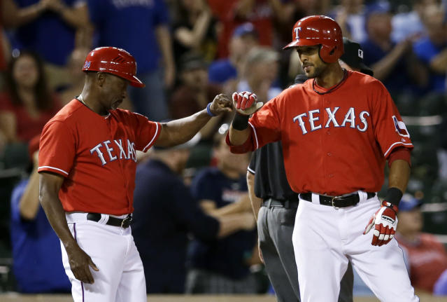 Texas Rangers third base coach Gary Pettis, left, congratulates Alex Rios on his RBI triple off of Houston Astros relief pitcher David Martinez in the sixth inning of a baseball game, Monday, Sept. 23, 2013, in Arlington, Texas. The triple completed the cycle for Rios. The Rangers won 12-0. (AP Photo/Tony Gutierrez)