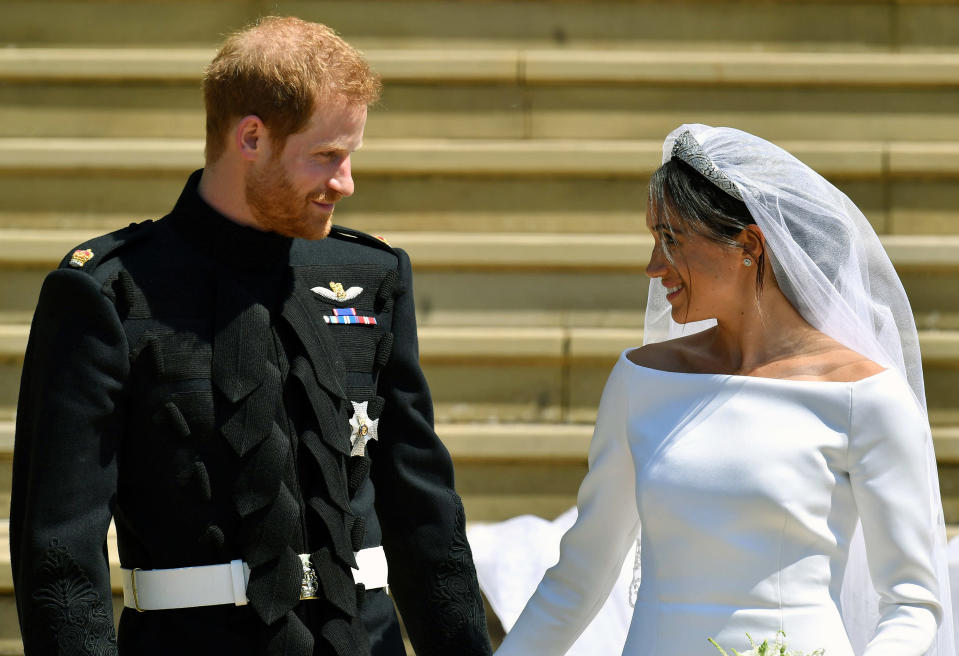 """FILE - In this Saturday, May 19, 2018 file photo, Britain's Prince Harry and Meghan Markle walk down the steps after their wedding at St. George's Chapel in Windsor Castle in Windsor, England. In a stunning declaration, Britain's Prince Harry and his wife, Meghan, said they are planning """"to step back"""" as senior members of the royal family and """"work to become financially independent."""" A statement issued by the couple Wednesday, Jan. 8, 2020 also said they intend to """"balance"""" their time between the U.K. and North America (Ben Birchhall/pool photo via AP, file)"""