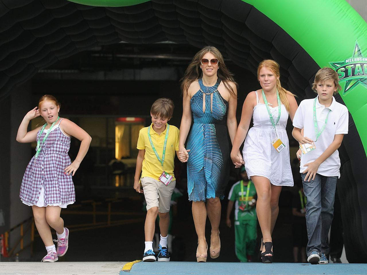 MELBOURNE, AUSTRALIA - DECEMBER 17:  Liz Hurley walks out to toss the coin with her son Damian (yellow) and Shane Warne's children Brooke, Summer (dancing) and Jackson ahead of the T20 Big Bash League match between the Melbourne Stars and the Sydney Thunder at Melbourne Cricket Ground on December 17, 2011 in Melbourne, Australia.  (Photo by Hamish Blair/Getty Images)