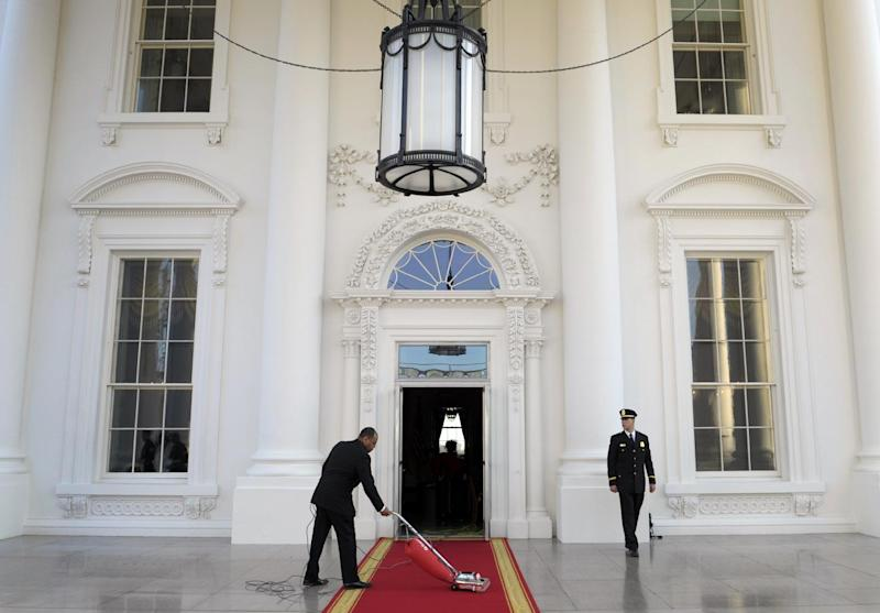 FILE - In this March 14, 2012, file photo, the red carpet of the North Portico is prepared for President Barack Obama and first lady Michelle Obama to welcome Britain's Prime Minister David Cameron and his wife Samantha to the White House for a State Dinner in Washington. Obama is using privileged access to one of America's greatest landmarks to reward his most generous financial supporters in ways that Republicans Mitt Romney and Rick Santorum can't match: More than 60 of Obama's biggest campaign donors have visited the White House more than once for meetings with top advisers, holiday parties or state dinners, a review by The Associated Press has found. (AP Photo/Susan Walsh, File)
