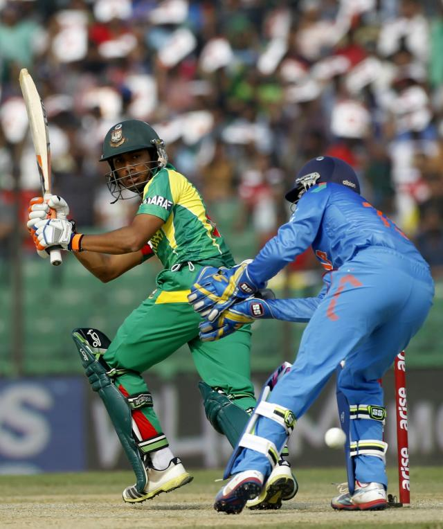 Bangladesh's Anamul Haque (L) plays the ball as India's wicketkeeper Dinesh Karthik tries to catch it during their Asia Cup 2014 one-day international (ODI) cricket match in Fatullah February 26, 2014. REUTERS/Andrew Biraj (BANGLADESH - Tags: SPORT CRICKET)