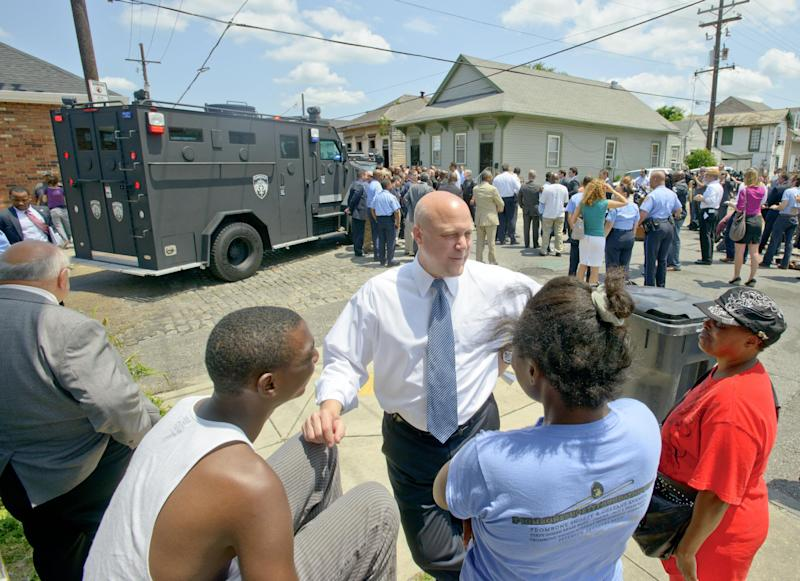 FILE - In this May 16, 2013. New Orleans Mayor Mitch Landrieu greets with residents before a news conference at North Villere and Frenchman Streets, where 20 people were shot in a the parade on Mother's Day in New Orleans. Gunfire one boozy Mardi Gras weekend, a mass shooting at a jazz music parade and the gunshot deaths of three children in 2013 nearly overshadowed a promising statistic New Orleans Mayor Mitch Landrieu touts as he seeks re-election Saturday: the city's murder rate dropped last year by nearly 20 percent. Still, the violence stubbornly continues and crime is a major election issue as Landrieu seeks four more years. Though many voters say they still don't feel safe, local pundits say Landrieu is positioned to beat two fellow Democrats, with a runoff date of March 15 if needed. (AP Photo/Matthew Hinton, file)