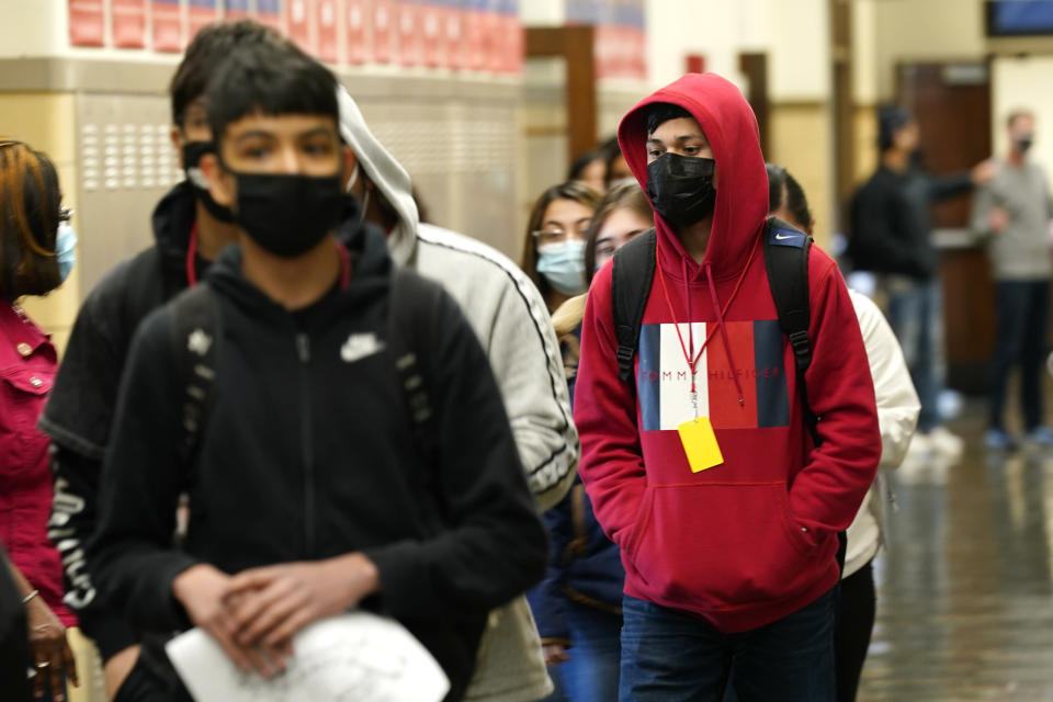 FILE - In this March 31, 2021, file photo, students at Wyandotte County High School wear masks as the walk through a hallway on the first day of in-person learning at the school in Kansas City, Kan. With a massive infusion of federal aid coming their way, schools across the U.S. are weighing how to use the windfall to ease the harm of the pandemic — and to tackle problems that existed long before the coronavirus. (AP Photo/Charlie Riedel, File)
