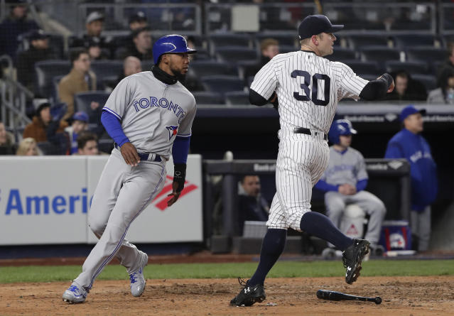 Toronto Blue Jays' Teoscar Hernandez, left, scores on a base hit by Curtis Granderson as New York Yankees pitcher David Robertson (30) look to back up a throw home during the eighth inning of a baseball game Thursday, April 19, 2018, in New York. (AP Photo/Julie Jacobson)