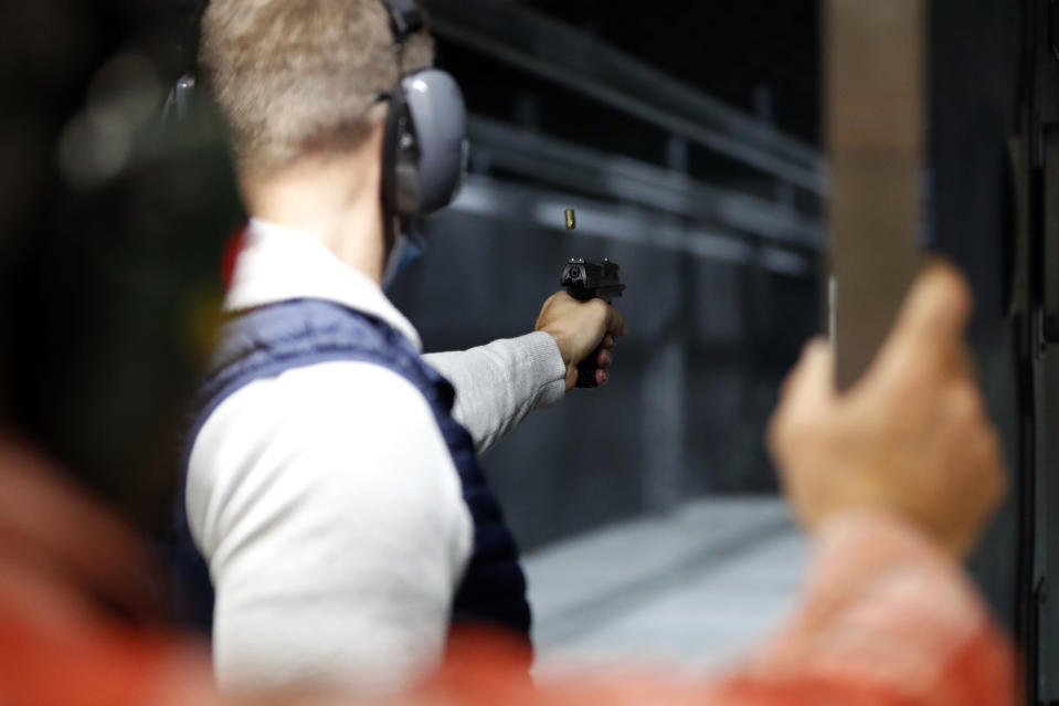 Chicago resident Ray Mandel practices shooting during a session at Maxon Shooter's Supplies and Indoor Range, Friday, April 30, 2021, in Des Plaines, Ill. After a year of pandemic lockdowns, mass shootings are back, but the guns never went away. As the U.S. inches toward a post-pandemic future, guns are arguably more present in the American psyche and more deeply embedded in American discourse than ever before. The past year's anxiety and loss fueled a rise in gun ownership across political and socio-economic lines. (AP Photo/Shafkat Anowar)