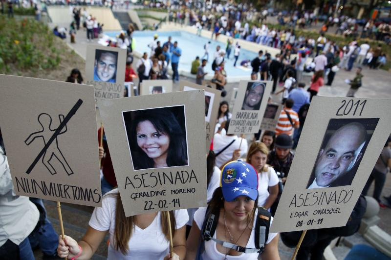 Opposition students hold photographs of victims of violence during a protest in Caracas