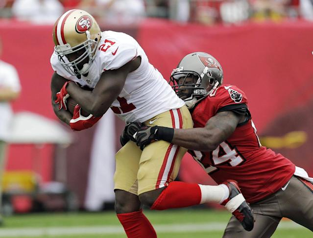 FILE - In this Dec. 15, 2013, file photo, San Francisco 49ers running back Frank Gore (21) is grabbed by Tampa Bay Buccaneers cornerback Darrelle Revis (24) during the first quarter of an NFL football game in Tampa, Fla. The New England Patriots announced Monday, March 17, 2014, the signing of the three-time All-Pro cornerback Revis. (AP Photo/Chris O'Meara, File)