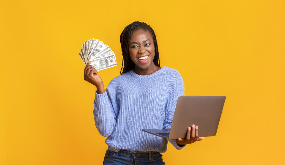 Young black woman holding cash and laptop in hands in front of a yellow background.