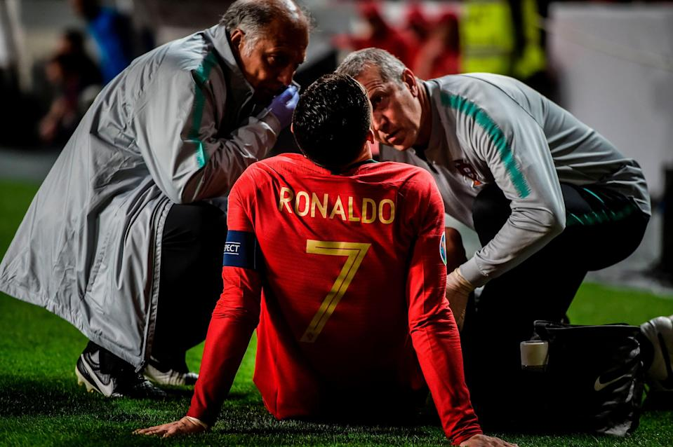 Doctors check on Portugal's forward Cristiano Ronaldo during the Euro 2020 qualifying group B football match between Portugal and Serbia at the Luz stadium in Lisbon on March 25, 2019. (Photo by PATRICIA DE MELO MOREIRA / AFP)        (Photo credit should read PATRICIA DE MELO MOREIRA/AFP/Getty Images)