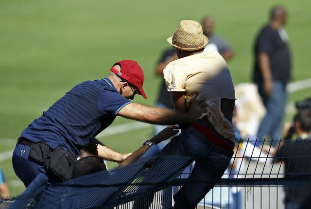 A security guard stops a fan of Portugal's Cristiano Ronaldo from disrupting the team training session in Campinas, June 12, 2014. Portugal is preparing for their first soccer match of the 2014 World Cup against Germany on June 16. REUTERS/Mauro Horita (BRAZIL - Tags: SPORT SOCCER WORLD CUP)