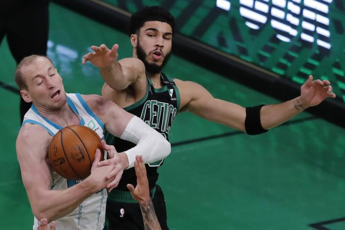 Boston Celtics' Jayson Tatum, right, and Charlotte Hornets' Cody Zeller battle for the ball during the first half of an NBA basketball game, Sunday, April 4, 2021, in Boston. (AP Photo/Michael Dwyer)