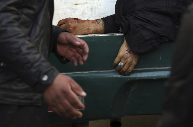 <p>A man passes the hand of a deceased woman on a stretcher in a hospital following a suicide attack in Kabul, Afghanistan, Thursday, Dec. 28, 2017. (Photo: Rahmat Gul/AP) </p>