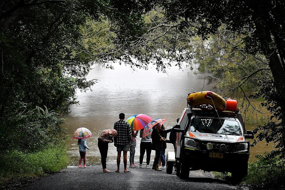 <p>Residents — with umbrellas up — look back at the flooded roads of Richmond on Monday.</p>