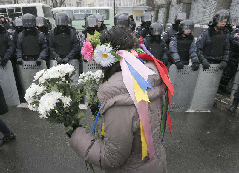 A pro-European union activist presents flowers to police officers at Presidential office in Kiev, Ukraine, Sunday, Dec. 8, 2013. Thousands of Ukrainians angered by the president's turn away from Europe and by police violence are heading for the center of the capital for a mass rally. (AP Photo/Efrem Lukatsky)
