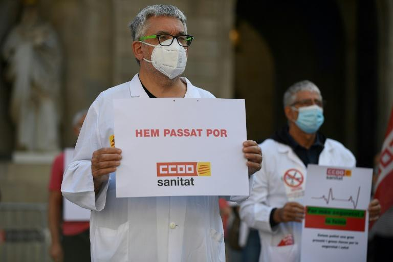 """A healthcare worker holds a sign reading """"we have been through fear"""" during a demonstration in Barcelona as millions of Spaniards face up to latest measures including restriction of movement between the regions"""