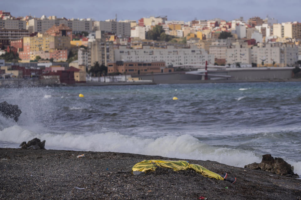 The body of a young man is covered with an emergency blanket after being recovered by Spanish police from waters near the border between Morocco and Spain's north African enclave of Ceuta, Thursday, May 20, 2021. Thousands of migrants jumped or swam around a border fence to reach European soil this week after Morocco loosened its border patrols. (AP Photo/Bernat Armangue)